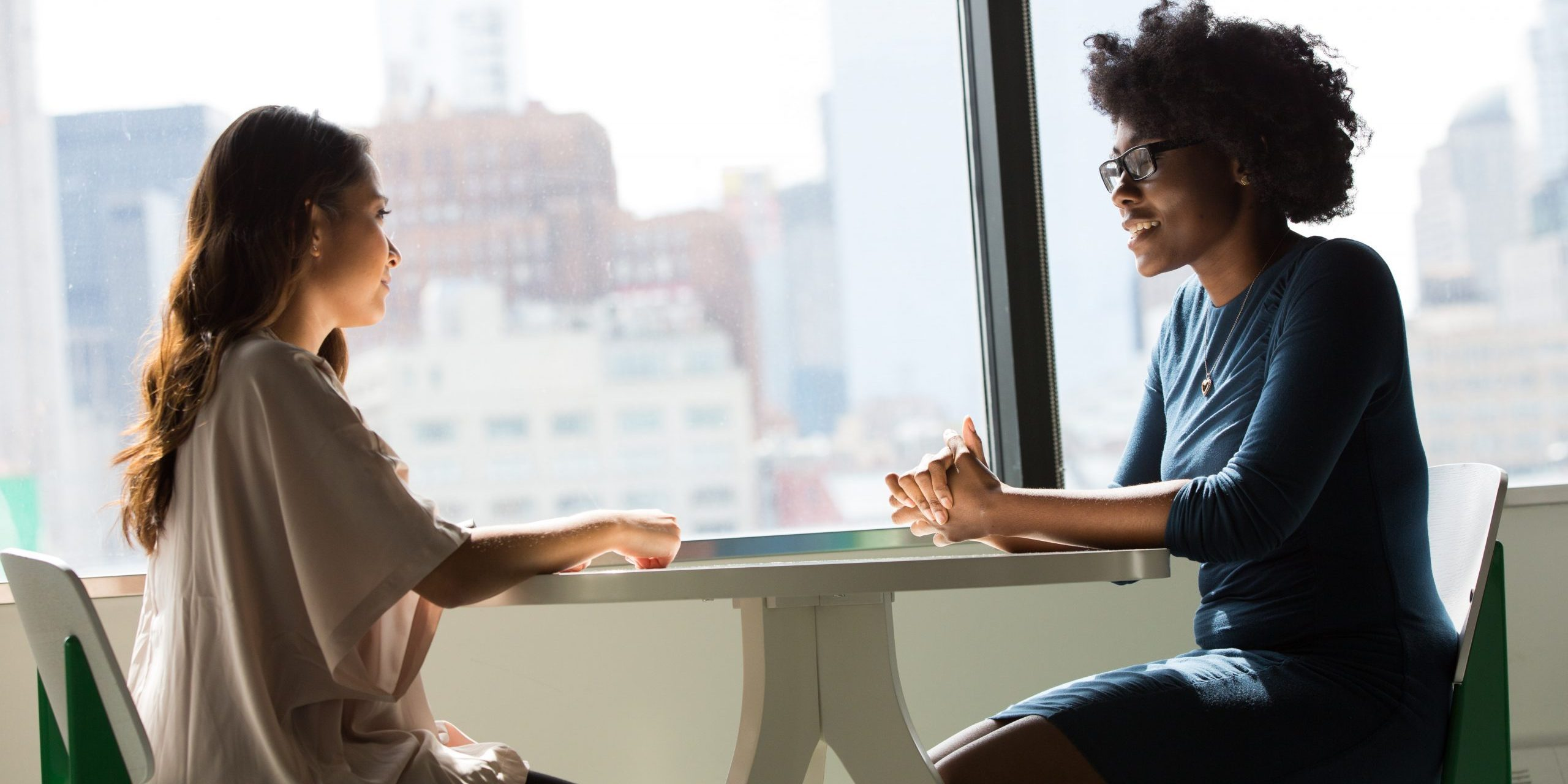 two women at a table talking about web design